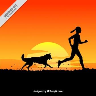 Antecedentes da mulher e do cão correndo em uma paisagem por do sol