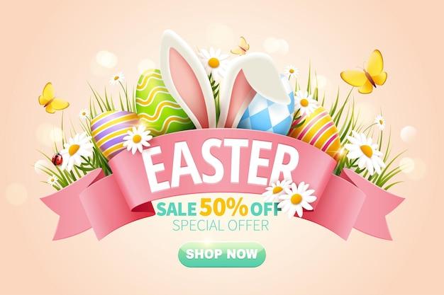 Anúncios pop-up de venda de páscoa com orelha de coelho e ovos de páscoa na grama em fundo rosa