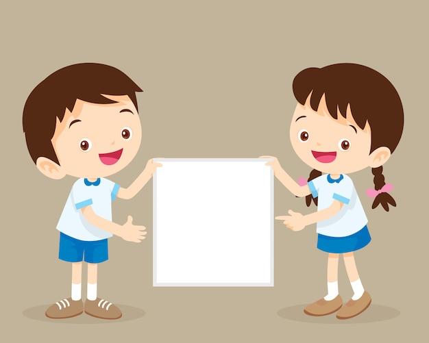 Apresentação infantil. menino bonito e menina do estudante que guardam a apresentação da placa.