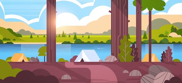 Área de camping barracas na floresta acampamento de verão dia ensolarado nascer do sol paisagem natureza com água montanhas e colinas