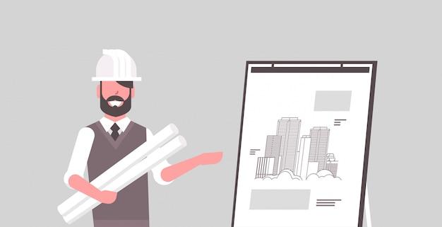 Arquiteto de homem no capacete segurando plantas em engenheiro de rolos, mostrando o novo desenho de edifício em cavalete