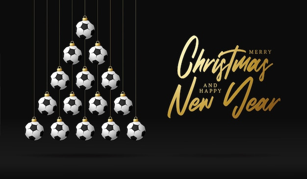 Árvore de bugigangas de cartão de natal e ano novo futebol. árvore de natal criativa feita por bola de futebol em fundo preto para a celebração do natal e ano novo. cartão esportivo