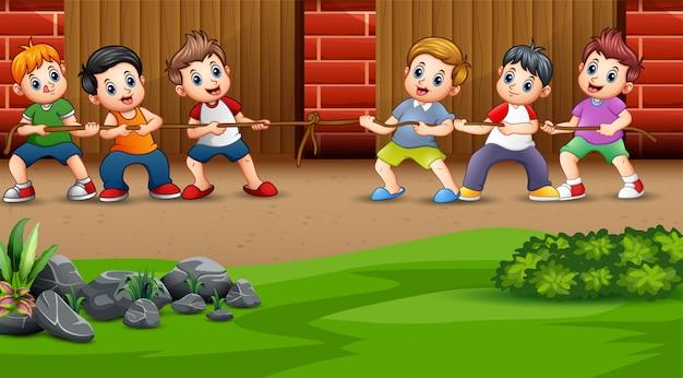 As crianças brincam cabo de guerra no quintal