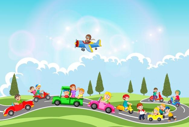 As crianças brincam com o carro e outro transporte no lindo dia