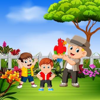 As crianças brincam com seu tio e o pássaro no jardim