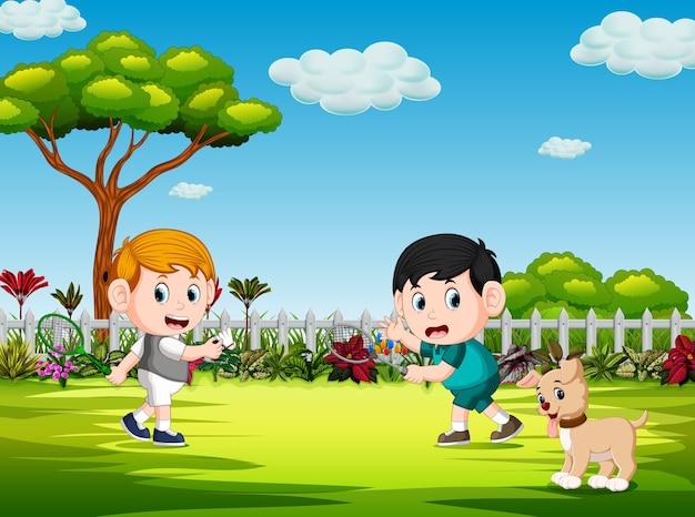 As crianças brincam de badminton e o cão