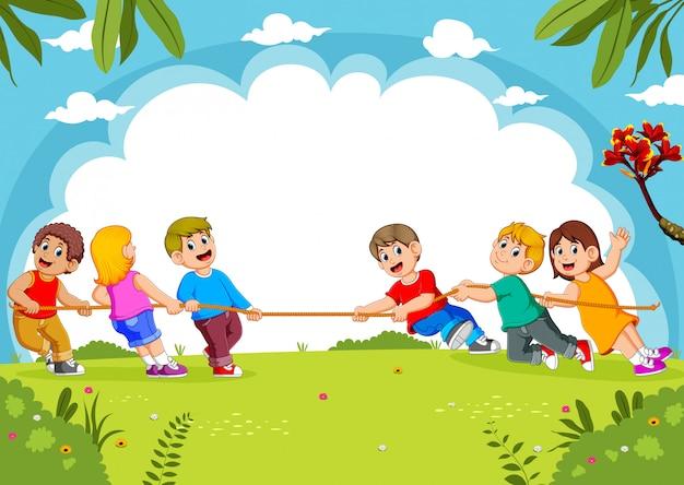 As crianças brincam de cabo de guerra no parque