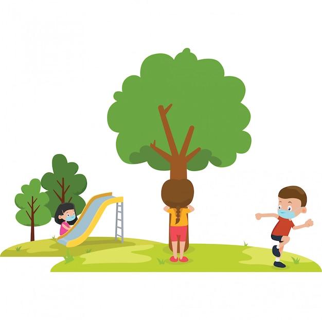 As crianças brincam de esconde-esconde no parque enquanto usam máscara médica
