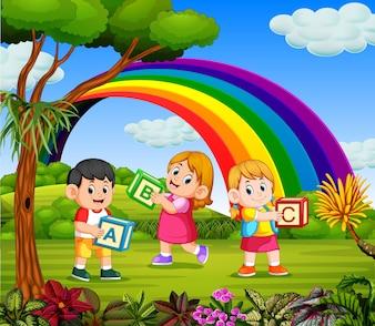 As crianças brincam e seguram sua caixa de alfabeto