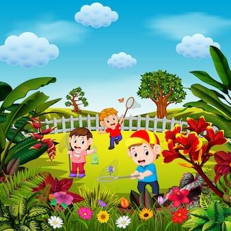 As crianças brincam para pegar a borboleta no quintal