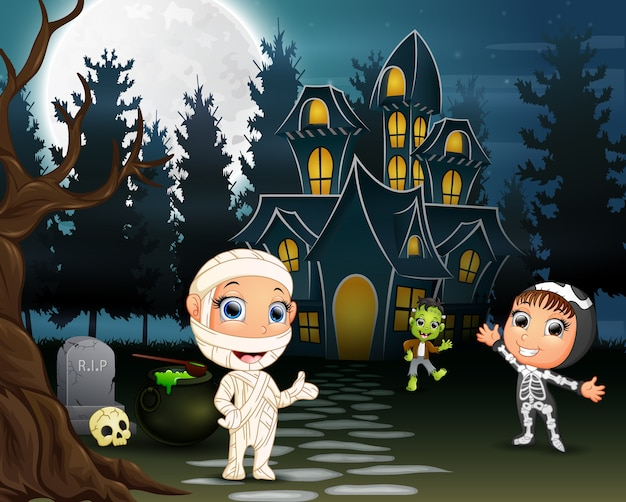 As crianças celebram uma festa de halloween ao ar livre à noite