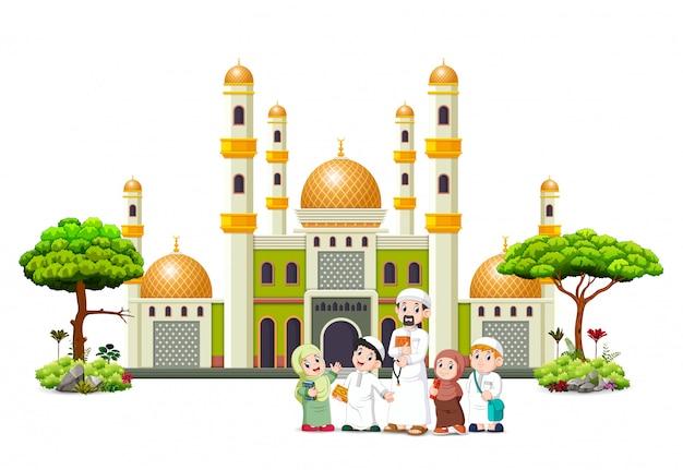 As crianças com o pai estão posando em frente à mesquita verde
