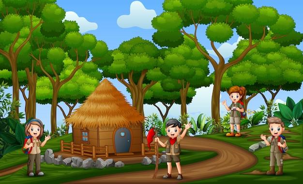 As crianças de escoteiros, caminhadas na paisagem rural Vetor Premium