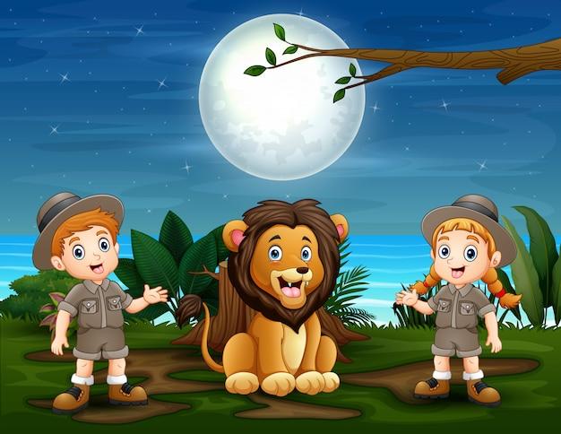 As crianças do safari com leão na natureza