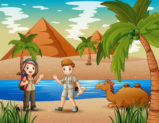 As crianças escoteiras acampando no deserto Vetor Premium