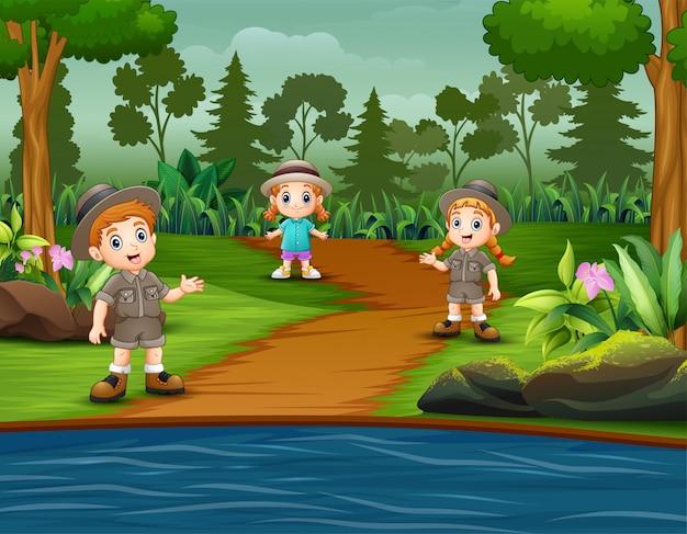 As crianças escoteiras estão explorando a floresta