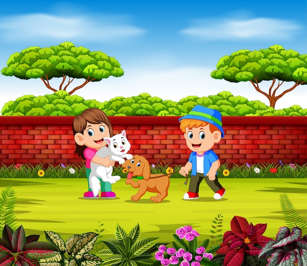 As crianças estão brincando com seus animais de estimação perto da parede vermelha