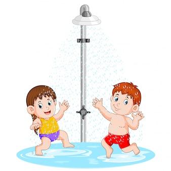 As crianças estão brincando debaixo do chuveiro