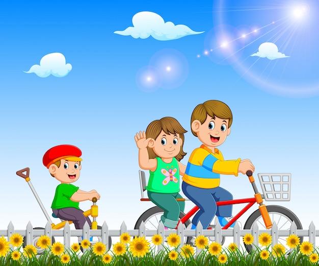 As crianças estão brincando e andando de bicicleta juntos no jardim