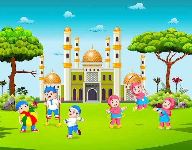 As crianças estão brincando no quintal perto da mesquita
