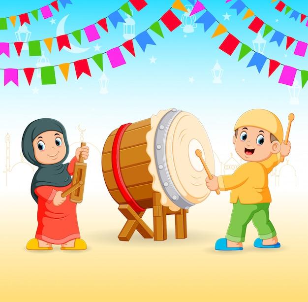 As crianças estão chapeando as ferramentas de música e o tambor para o evento do ramadã