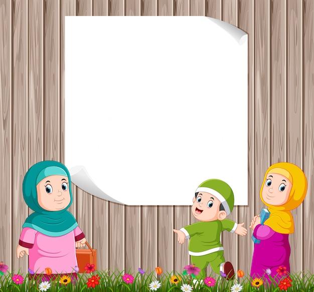 As crianças estão de pé e brincando com sua mãe perto da placa em branco