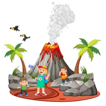As crianças estão fazendo férias e tirando uma foto perto do vulcão