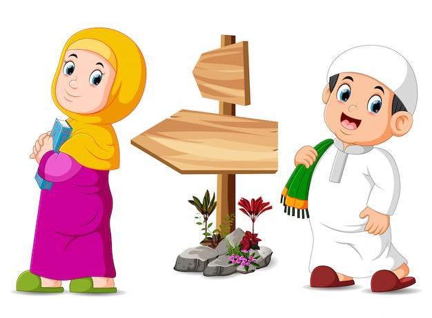 As crianças estão posando perto da placa de madeira