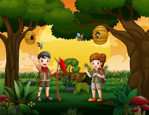 As crianças explorador caminhadas na madeira