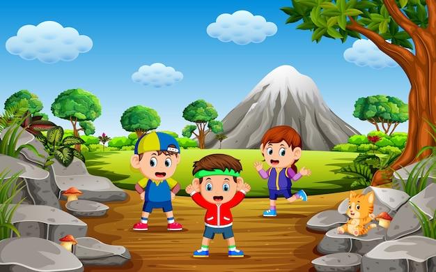 As crianças fazem desporto na floresta perto da montanha de rocha com um monte de árvores
