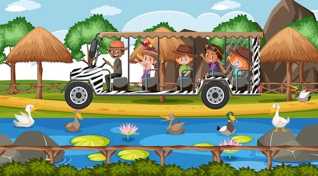 As crianças fazem um tour na cena do safari com muitos patos no lago