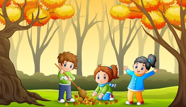 As crianças limpam as folhas caídas no jardim