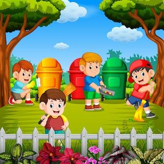 As crianças limpam o jardim e jogam o lixo em uma lixeira nas três cores