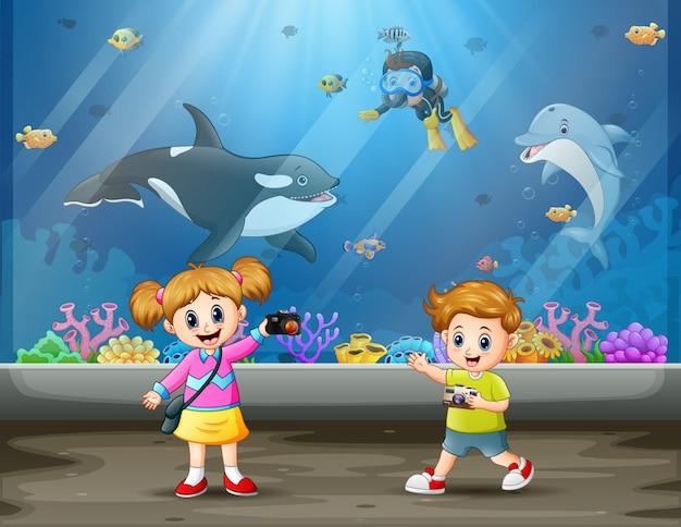 As crianças tiram fotos no aquário