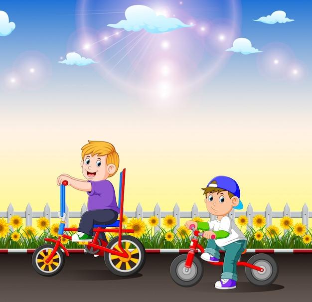 As duas crianças estão andando de bicicleta à tarde