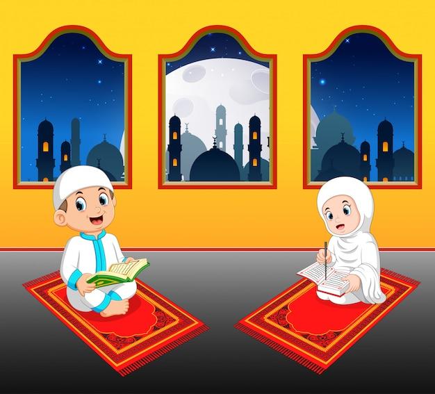 As duas crianças estão lendo al quran em seu tapete de oração perto da janela