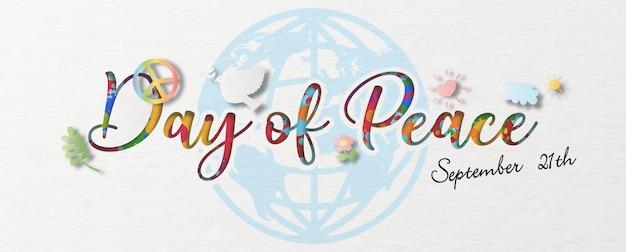 As letras do dia e do nome com o objeto da paz em papel recortado em estilo e padrão colorido no fundo azul do papel global e branco.