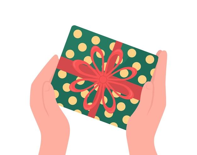 As mãos dão um objeto de cor para presente embrulhado. presente de natal com laço de fita.