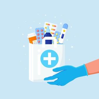 As mãos do correio em luvas descartáveis seguram um saco de papel com um frasco de comprimidos, remédios e termômetro dentro.