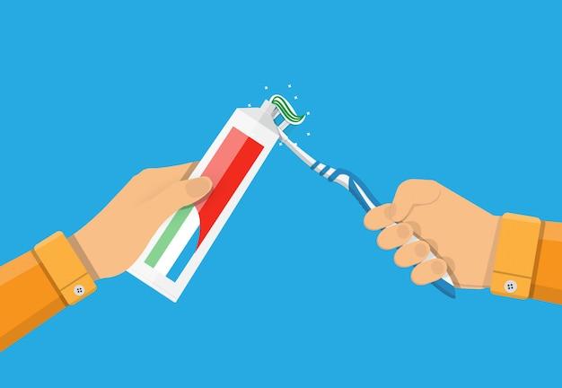 As mãos usam creme dental e uma escova de dentes