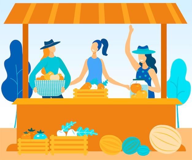 As mulheres vendem na feira de agricultores legumes e frutas