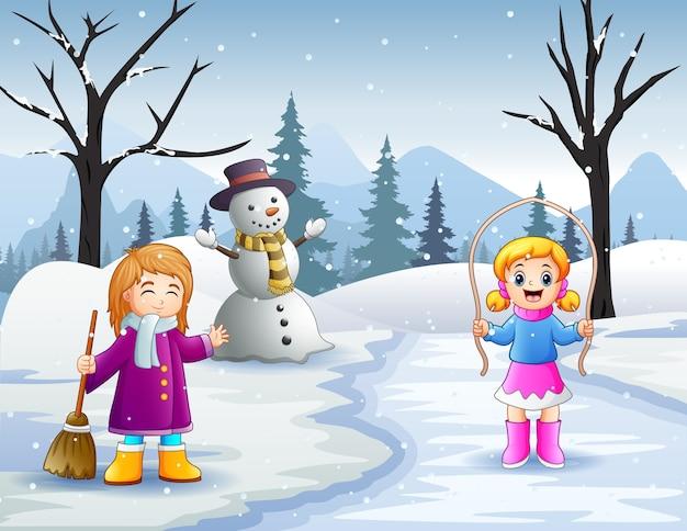 Atividade de duas meninas ao ar livre em paisagem de inverno com neve