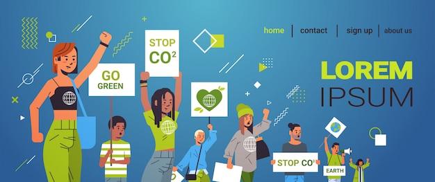 Ativistas ambientais segurando cartazes vão verde, excepto o planeta greve conceito misturam manifestantes de raça que fazem campanha para proteger a terra demonstrando contra o aquecimento global retrato cópia espaço horizontal