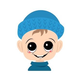 Avatar de uma criança com olhos grandes e um sorriso largo em um chapéu de malha azul. um lindo garoto com um rosto alegre em um cocar outonal ou de inverno. cabeça de criança adorável com emoções felizes