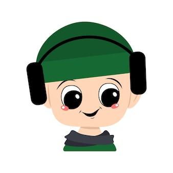 Avatar de uma criança com olhos grandes e um sorriso largo em um chapéu verde com fones de ouvido. um lindo filho com um rosto alegre em um lenço e um cocar outonal ou de inverno. cabeça de bebê adorável com emoções felizes