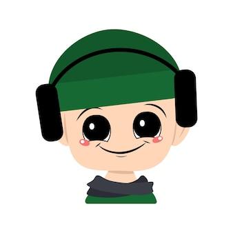 Avatar de uma criança com olhos grandes e um sorriso largo em um chapéu verde com fones de ouvido. um lindo garoto com um rosto alegre em um lenço e um cocar outonal ou de inverno. cabeça de bebê adorável com emoções felizes