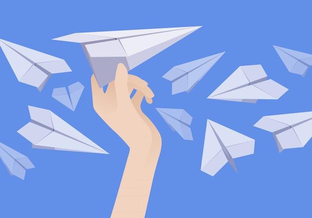 Avião de papel branco na mão feminina e outros aviões nas proximidades