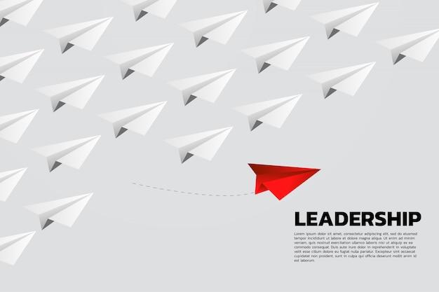 Avião de papel origami vermelho saindo do grupo de branco