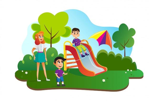 Babá com crianças em slide, menino com pipa.