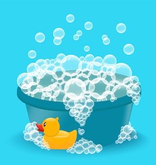 Bacia azul com espuma de sabão e pato de borracha amarelo. lavar roupas de bebê ou tomar banho.